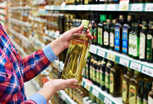 person looking at bottle of oil