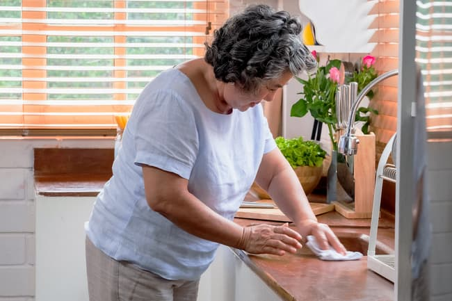 photo of mature woman cleaning counter