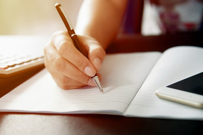 photo of person writing in journal