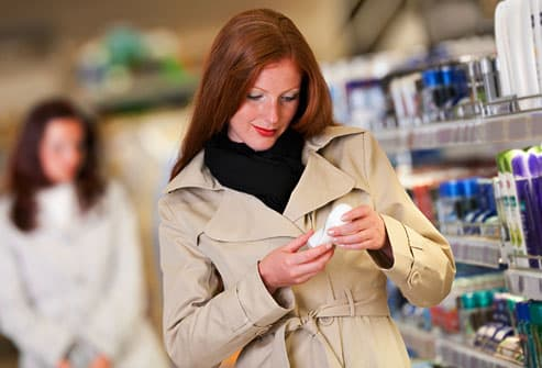 Woman reading deodorant label in drugstore