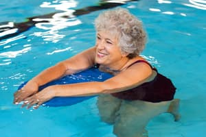 photo of mature woman exercising in pool