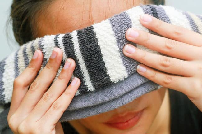 woman holding washcloth to eyes