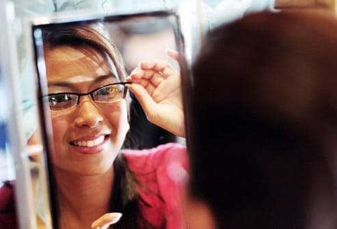 smiling woman trying on glasses