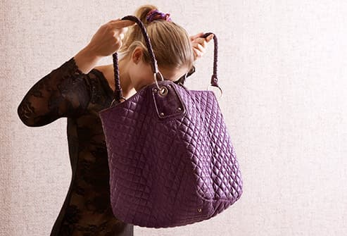 woman digging in large handbag