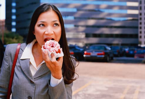 Businesswoman standing outdoors, eating donut