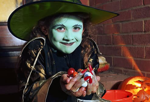 Girl in 'witch' halloween costume, holding candy