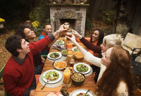 young adults raising toast at dinner party