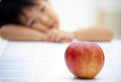 child staring at apple