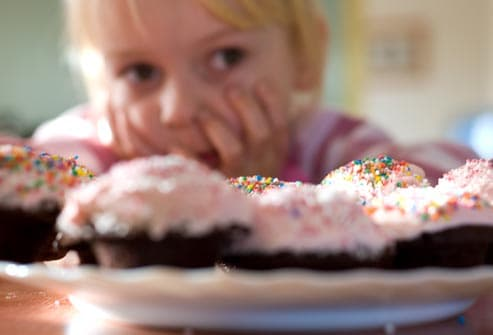little girl staring at cupcakes