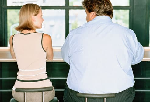 Petite woman and overweight businessman at table