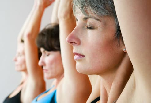 Three women doing yoga, close up