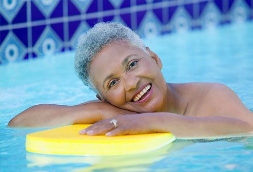 Mature woman in pool smiling with kick board