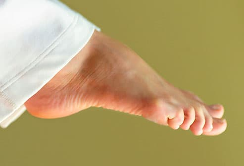 Young woman stretching feet, close-up on foot