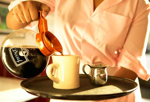 Waitress pouring cup of decaf coffee