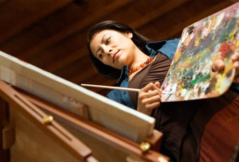 Woman holding palette and painting at easel