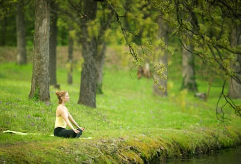 Woman meditating on the bank of a river