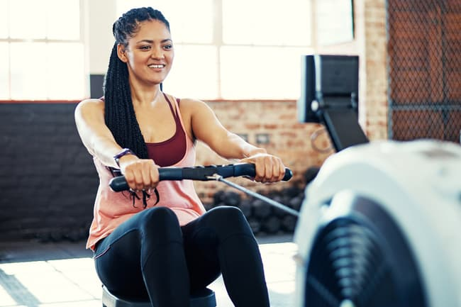 photo of woman using rowing machine