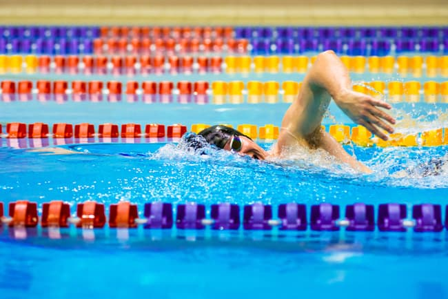 photo of man swimming laps