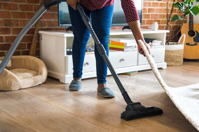 photo of woman vacuuming floor