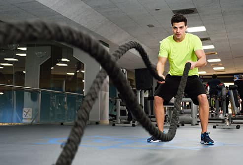man working battle ropes