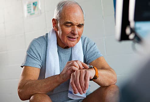 man looking at watch during workout