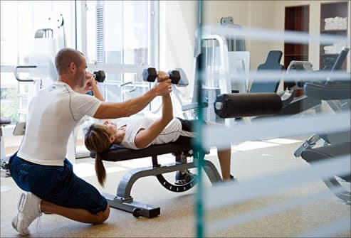 trainer assisting woman with weights