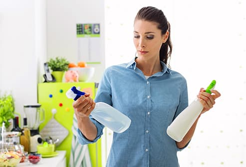 woman choosing cleaner spray