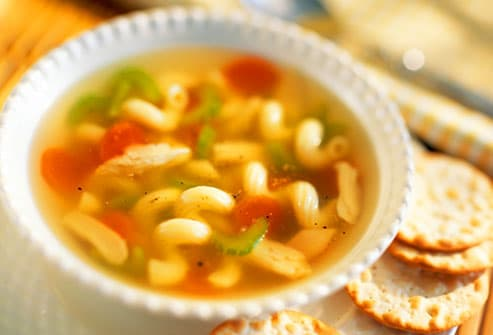 Bowl of chicken soup with crackers
