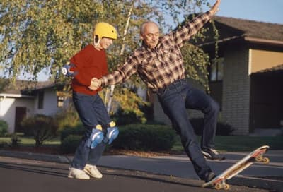 teen helping older man balance on skateboard