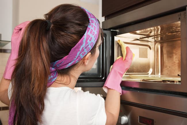 photo of woman cleaning microwave oven