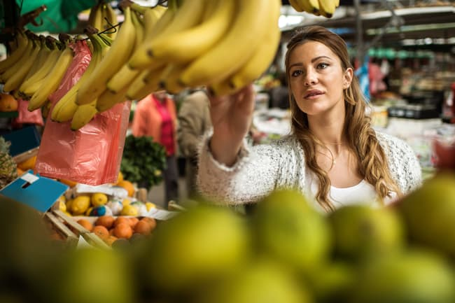 woman selecting bananas at grocery store