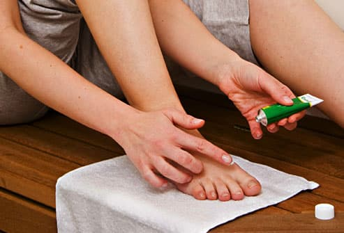 Woman applying ointment to foot