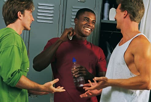 Three men laughing in a locker room