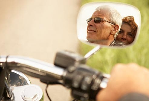 mature couple in motorcycle rearview mirror