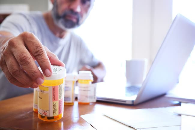 photo of man reading medication bottle