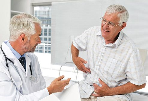 man describing stomach pain to doctor