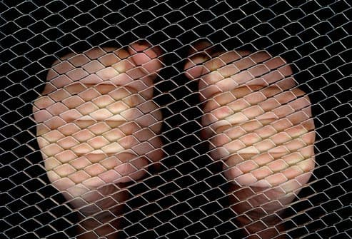 clenched fists behind cage