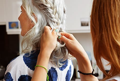woman braiding grey hair