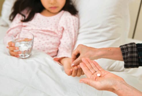 mother giving pills to daughter