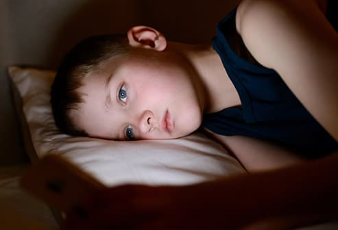 boy using smartphone in bed