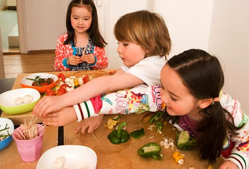 Three kids making veggie treats on table
