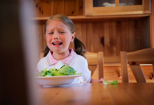 Girl crying at table over bowl of veggies