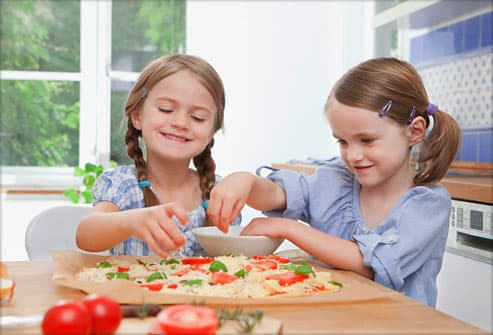 Two girls adding veggies to pizza