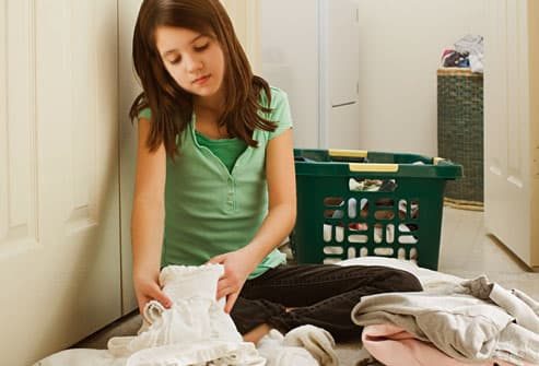 Preteen girl washing undergarments