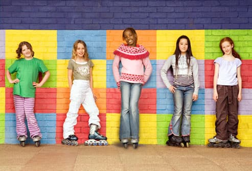 Preteen girls lined up on wall