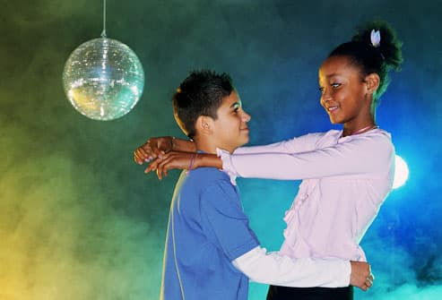 Preteen boy and girl dancing