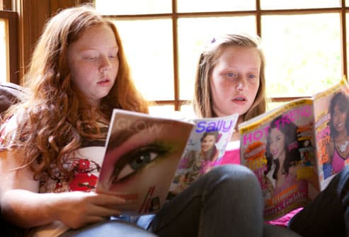 Teen girls reading fashion mags