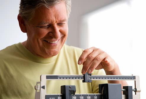Mature man moving slider on medical scale