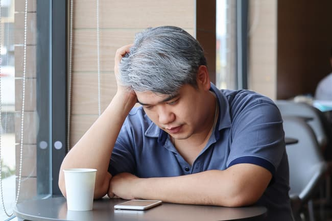 photo of tired man in cafe