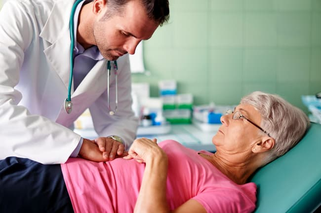 doctor checking patients stomach